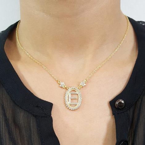 colar pingente oval com letra e centro vazado borda cravejada com zirconias e 2 flores na corrente joia folheada a ouro foto no pescoso brilho folheados