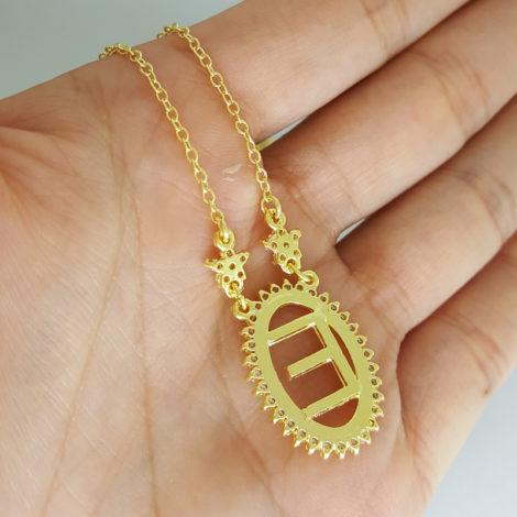 colar pingente oval com letra e centro vazado borda cravejada com zirconias e 2 flores na corrente joia folheada a ouro foto verso do colar na mao brilho folheados