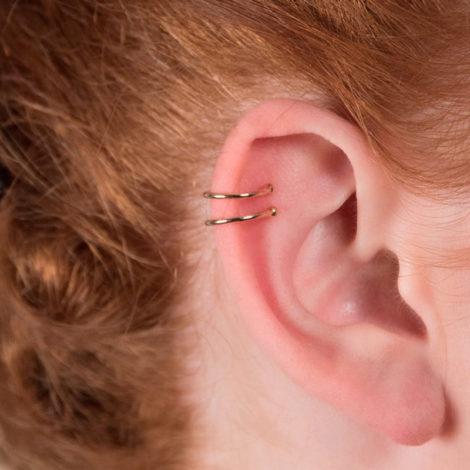525891 Brinco earcuff formado por 2 aros vazado aberto com esferas nas pontas joia folheada a ouro rommanel brilho folheados foto do piercing na orelha da modelo