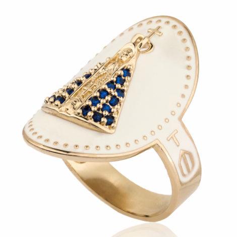 Imagem de fundo branco, com anel oval dourado de nossa senhora aparecida, visto da lateral, contendo manto cravejado em zircônia azul. Na lateral dá para visualizar cruz delicada em metal dourado.