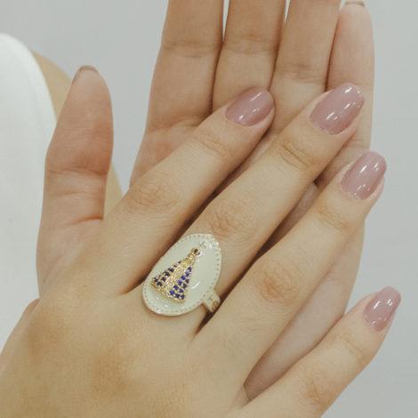 Foto das mãos de uma mulher de pele clara, com unhas em rosa nude,usando o anel de nossa senhora aparecida oval, em resina branca, com manto em zircônia azul. Foto está demonstrando como fica o anel em uso real.