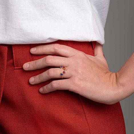 Foto com uma mulher de pele clara, pegando a parte lateral do quadril com uma mão sobreposta ao quadril, demonstrando o uso do anel 512923 da Rommanel. Anel formato v contendo cinco zircônias triangulares coloridas, sendo duas azuis, duas rosas e uma laranja. Anel esta no dedo anelar da modelo.