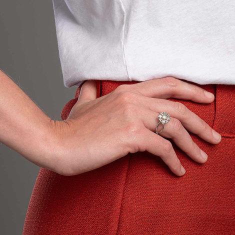 Foto com uma mulher de pele clara, pegando a parte lateral do quadril com uma mão sobreposta ao quadril, demonstrando o uso do anel 110866 da Rommanel. Anel na cor dourada folheado a ródio no formato de buque de flores contendo quarenta e três zircônias brancas de 1,0 mm. Anel com as laterais aberta tendo um encontro de aro na parte de baixo do anel. Anel esta no dedo anelar da modelo.