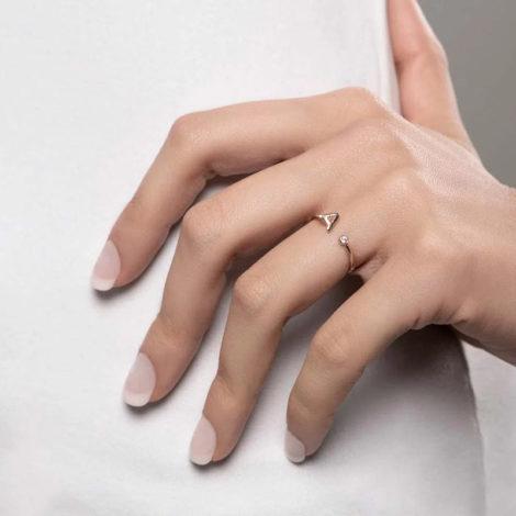 Foto com uma mulher de pele clara, com uma mão sobreposta a cintura, demonstrando o uso do anel 512843 da Rommanel. Anel na cor dourada folheado a ouro, anel ajustável formado por letra A de um lado e 1 zircônia de 2,0 mm do outro lado. Anel esta no dedo anelar da modelo.