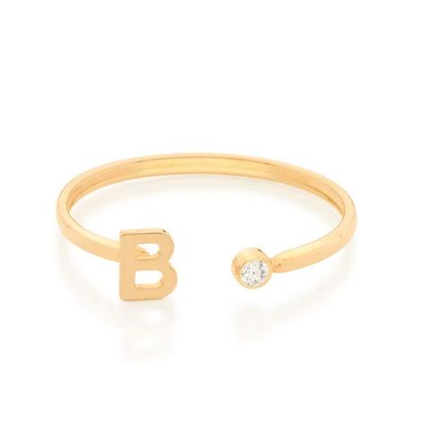 Imagem de fundo branco com um anel no centro da marca Rommanel, código 512843. Anel na cor dourada folheado a ouro, anel ajustável formado por letra B de um lado e 1 zircônia de 2,0 mm do outro lado.