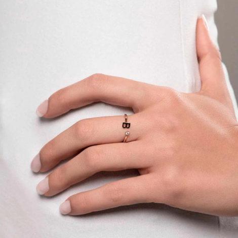 Foto com uma mulher de pele clara, com uma mão sobreposta a cintura, demonstrando o uso do anel 512843 da Rommanel. Anel na cor dourada folheado a ouro, anel ajustável formado por letra B de um lado e 1 zircônia de 2,0 mm do outro lado. Anel esta no dedo médio da modelo.