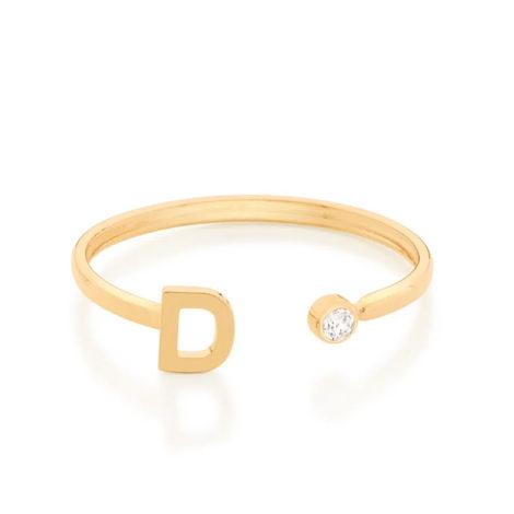 Imagem de fundo branco com um anel no centro da marca Rommanel, código 512843. Anel na cor dourada folheado a ouro, anel ajustável formado por letra D de um lado e 1 zircônia de 2,0 mm do outro lado.