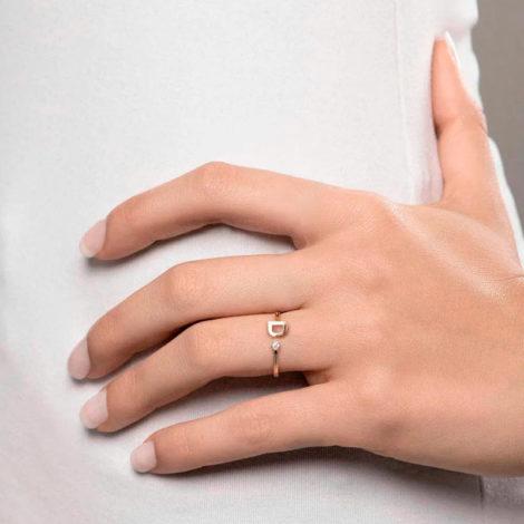 Foto com uma mulher de pele clara, com uma mão sobreposta a cintura, demonstrando o uso do anel 512843 da Rommanel. Anel na cor dourada folheado a ouro, anel ajustável formado por letra D de um lado e 1 zircônia de 2,0 mm do outro lado. Anel esta no dedo anelar da modelo.