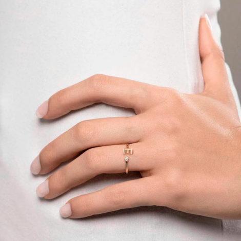 Foto com uma mulher de pele clara, com uma mão sobreposta a cintura, demonstrando o uso do anel 512843 da Rommanel. Anel na cor dourada folheado a ouro, anel ajustável formado por letra E de um lado e 1 zircônia de 2,0 mm do outro lado. Anel esta no dedo anelar da modelo.