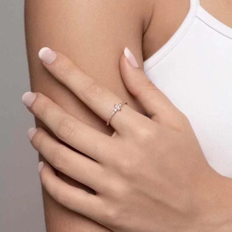Foto com uma mulher de pele clara, com uma mão sobreposta ao braço, demonstrando o uso do anel 512847 da Rommanel. Anel na cor dourada folheado a ouro, anel skinny ring Anel na cor dourada folheado a ouro, anel skinny ring cravejado com 24 zircônias, sendo 22 de 1,0 mm e 2 de 1,75 mm, com uma zircônia navete no centro com 2,5 x6 mm. Anel está no dedo anelar da modelo.
