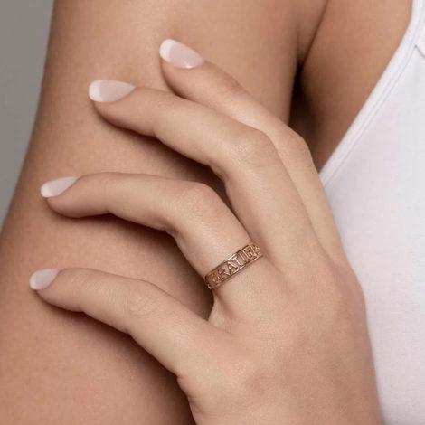 Foto com uma mulher de pele clara, com uma mão sobreposta ao braço, demonstrando o uso do anel 512850 da Rommanel. Anel na cor dourada folheado a ouro, anel skinny ring duplo aro escrito gratidão no centro. Anel está no dedo anelar da modelo.