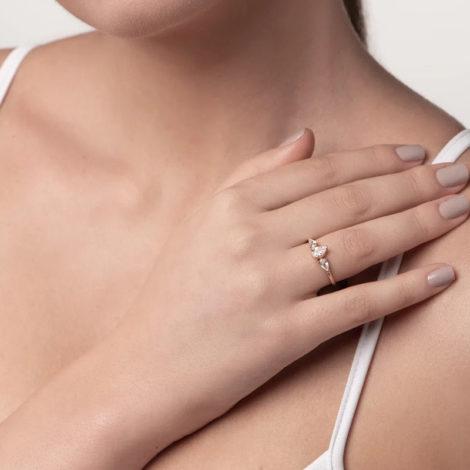 Foto com mulher de pela clara, pegando ângulo do queixo até o colo, com uma mão encostada próximo ao ombro para apresentar o uso do anel da rommanel 512852, anel aro fino e liso composto por três zircônias gotas, sendo duas com 3x5 mm e uma com 5x7 mm. Anel está no dedo anelar da modelo.