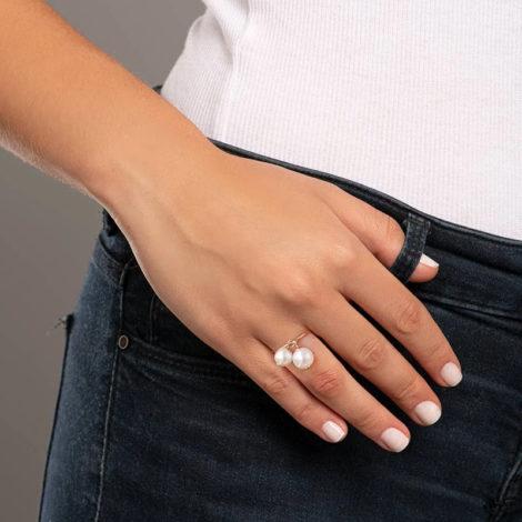 Foto com uma mulher de pele clara, pegando a parte lateral do quadril com uma mão apoiada ao quadril, demonstrando o uso do anel 512857 da Rommanel. Anel aro fino e liso contendo duas pérolas sintéticas penduradas. Anel está no dedo anelar da modelo.