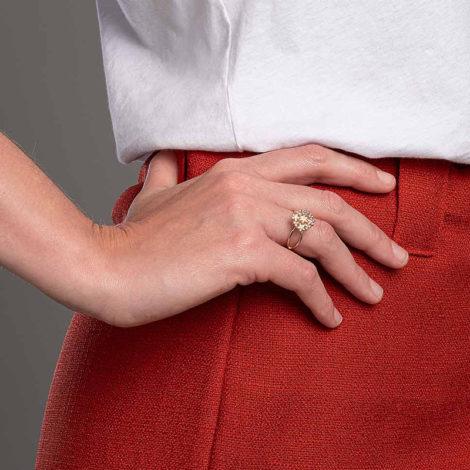 Foto com uma mulher de pele clara, pegando a parte lateral do quadril com uma mão sobreposta ao quadril, demonstrando o uso do anel 512916 da Rommanel. Anel . Anel esta no dedo anelar da modelo.