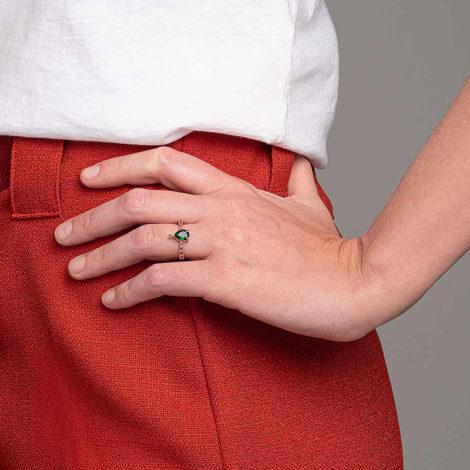 Foto com uma mulher de pele clara, pegando a parte lateral do quadril com uma mão sobreposta ao quadril, demonstrando o uso do anel 512920 da Rommanel. Anel composto por oito zircônias rosas disposto na metade de cima do aro, contendo uma zircônia gota verde escuro no centro. Anel esta no dedo anelar da modelo.