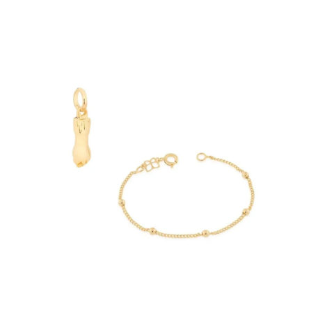 imagem de fundo branco contendo uma pulseira infantil bolinhas e pingente formato figa. Joia banhada a ouro 18k da marca Rommanel.