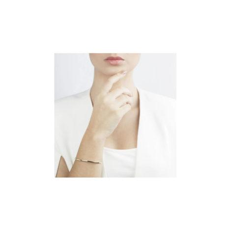 Foto com mulher de pele branca, direcionando a mão no queixo, com dedo indicado encostando suavemente no queixo. No pulso da mulher há um bracelete de aro fino, liso e dourado.