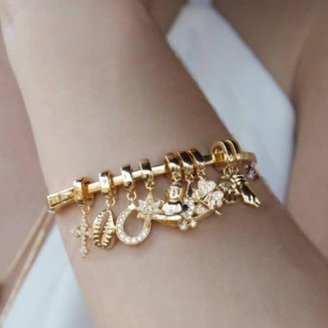 Foto com imagem do braço de uma modelo de pele branca, usando pulseira bracelete composta por vários berloques dourados da nova coleção Talismã da Sabrina Joias. São esses berloques no formato de cruz, búzio, ferradura, estrela, buda, olho grego, trevo e figa.