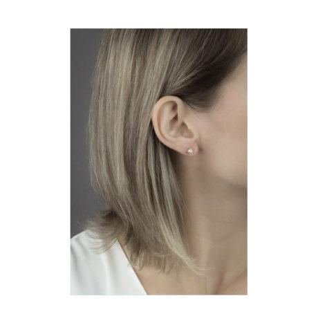 Imagem pegando parte do pescoço e orelha de uma modelo de pele clara, com cabelos com luzes e soltos, mostrando o uso do brinco ponto de luz com garras, banhado a ouro dourado, brinco mede 0,5 cm de diâmetro. Brinco da marca Sabrina Joias.