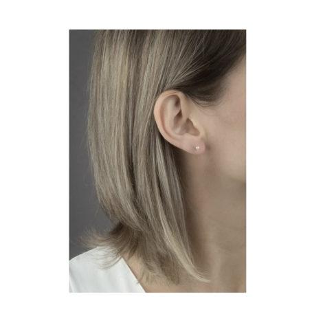 Imagem pegando parte do pescoço orelha de uma modelo de pele clara, com cabelos com luzes e soltos, mostrando o uso do brinco mini pérola com garras, banhado a ouro dourado, brinco mede 0,4 cm de diâmetro. Brinco da marca Sabrina Joias.